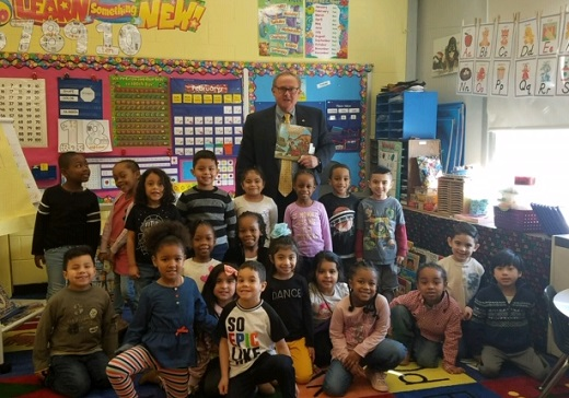 Councilman Cochrange stands alongside the entire Kintergarten class holding the book we is about to read as the smiling children's faces pose for the camera