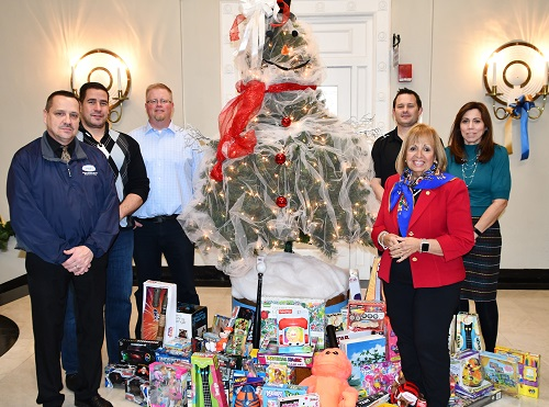 UPSEU and Baseline Health representatives, Tim Mare from the Youth Bureau and Town Supervisor Angie Carpenter pose infront of the 2nd floor Christmas tree with a large assortment of gifts surrounding it