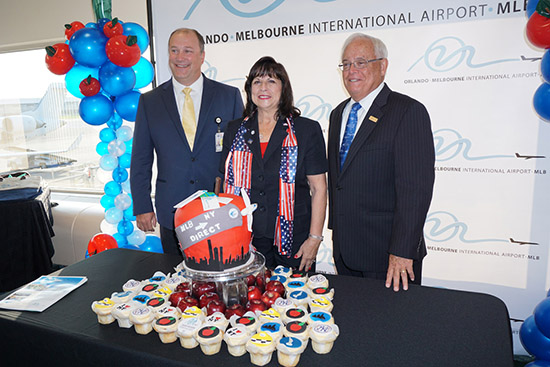 Melbourne officials and Elite Airways executives prepare to cut a celebratory cake