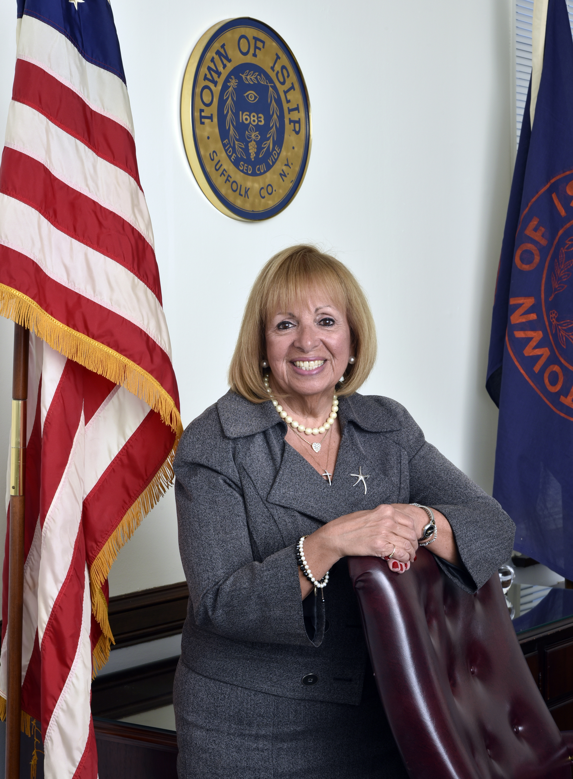 A picture of Supervisor Carpenter standing behind her desk in front of the Islip Town Seal, next to the American Flag